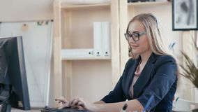电话中心雇员在工作在办公室 女孩接在电话的一个电话,键入在键盘,看 股票录像