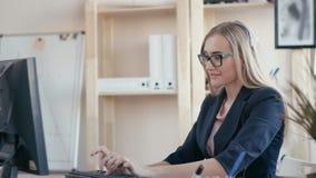 电话中心雇员在工作在办公室 女孩接在电话的一个电话,键入在键盘,看 影视素材