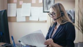 电话中心雇员在工作在办公室 有金发的一个女孩有坐在一张桌上的玻璃的在办公室 股票视频