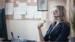 电话中心雇员在工作在办公室 有金发的一个女孩有坐在一张桌上的玻璃的在办公室 影视素材