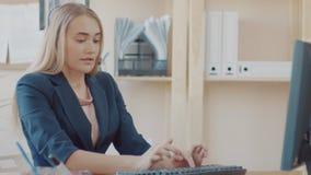 电话中心雇员在工作在办公室 有金发的一个女孩有玻璃的在办公室站立,举行 股票录像