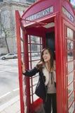 电话亭的愉快的少妇开门在伦敦,英国,英国 免版税图库摄影