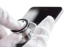 电话修理和服务概念 与听诊器的智能手机诊断 查出在白色 库存照片