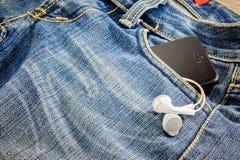电话和耳机在口袋斜纹布 免版税库存图片