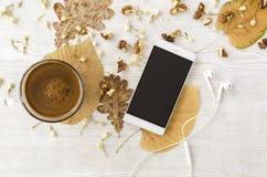 电话和耳机在土气桌上与叶子、核桃和咖啡 图库摄影