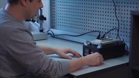 电话安装工在一个热板,PCB加热器上把一个白色智能手机放 影视素材