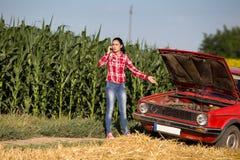 电话的女孩在残破的汽车旁边 库存图片