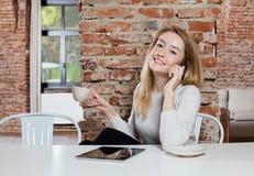 电话的女孩用咖啡 图库摄影