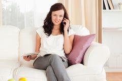 电话的妇女与在她的膝部的一本杂志 图库摄影