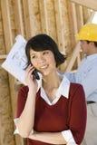 电话的妇女与建筑师在背景中 图库摄影