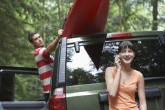 电话的妇女作为人在汽车屋顶的领带皮船 免版税库存图片