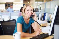 电话的妇女在繁忙的现代办公室 免版税库存照片