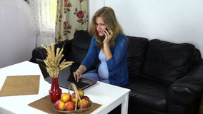 电话的妇女,当工作在膝上型计算机在舒适的家时 库存照片