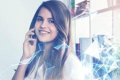 电话的微笑的年轻女实业家 免版税库存图片