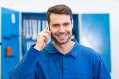 电话的微笑的技工 免版税图库摄影