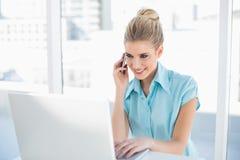电话的快乐的聪明的女实业家,当使用膝上型计算机时 库存图片