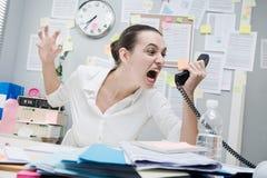 电话的恼怒的女实业家 免版税库存图片