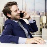 电话的愉快的商人在办公室在城市 免版税库存图片