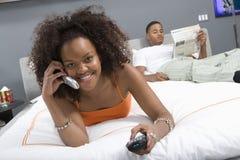 电话的愉快的妇女,当看电视在卧室时 免版税库存照片