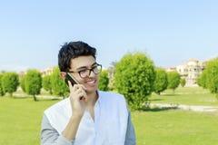 电话的愉快的年轻人有巨大微笑的 库存照片