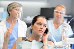 电话的无礼女实业家在牙齿办公室 库存照片