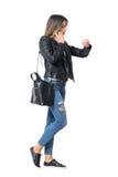 电话的检查在她的手表的繁忙的偶然时尚女孩侧视图时间 库存照片