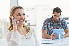 电话的白肤金发的妇女有后边她的同事的 免版税库存照片