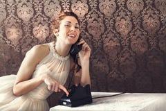 电话的美丽的少妇在客厅 免版税库存照片