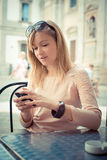 电话的美丽的白肤金发的妇女在酒吧 免版税库存照片
