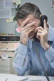 电话的被注重的雇员 库存照片