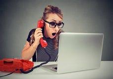 电话的震惊少妇使用在她的办公桌的便携式计算机 图库摄影