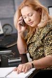 电话的高级妇女在办公室 库存照片
