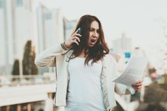 电话的,与大厦的纸女孩在背景 库存照片