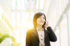 电话的年轻亚裔女商人 免版税库存图片