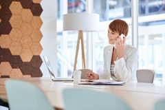 电话的年轻女实业家在她的书桌在现代办公室 图库摄影