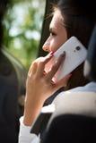 电话的年轻女实业家在她的汽车 图库摄影