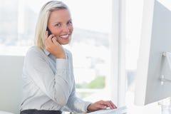 电话的年轻女实业家微笑对照相机的 免版税库存图片