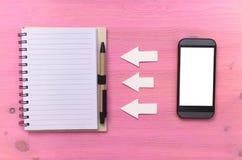 电话簿同步 请与邮件联系给我们打电话 电话美国 笔记本和手机有黑屏的在紫色木背景 免版税库存照片