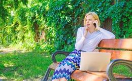 电话销售技术 销售主任在公园工作 有膝上型计算机的妇女工作得户外 最佳的销售主任总是拥有 免版税图库摄影
