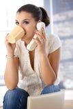 电话饮用的茶的俏丽的女孩 免版税库存照片