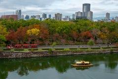 电车和巡航小船的访客享受秋天季节颜色的在大阪城公园在大阪,日本 免版税库存照片