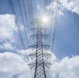 电送电线和定向塔现出轮廓反对蓝天和云彩、高压塔、光和增加的火光作用 库存图片