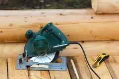 电通报锯和刀子在一个木平台 库存照片