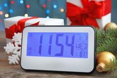 电钟、礼物和欢乐装饰在桌上 christmas countdown 免版税库存图片