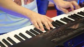 电钢琴,使用在键盘合成器钢琴钥匙的演员 音乐家弹奏在音乐会的一个乐器 股票视频