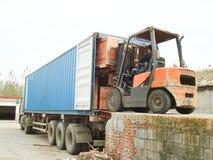 电铲车装货货物到容器里 库存照片