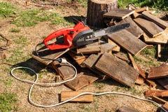 电锯和锯 电看见了在被锯的木材背景的链子  处理木头的概念导致燃料 库存照片