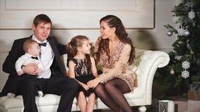 男人、妇女和他们的小孩基于一个白色沙发在Xmas晚上 影视素材