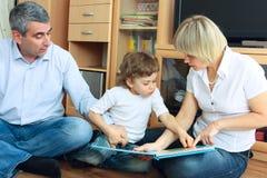 男人、妇女和小男孩阅读书 免版税库存照片