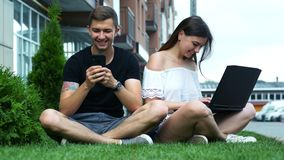 男人和使用一个手机和膝上型计算机的妇女,当坐草时 影视素材